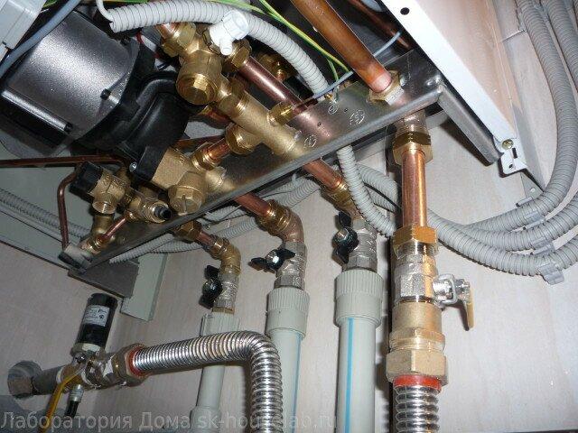 Вид снизу на котел NUVOLA-3 с подключенными водяными контурами и газом